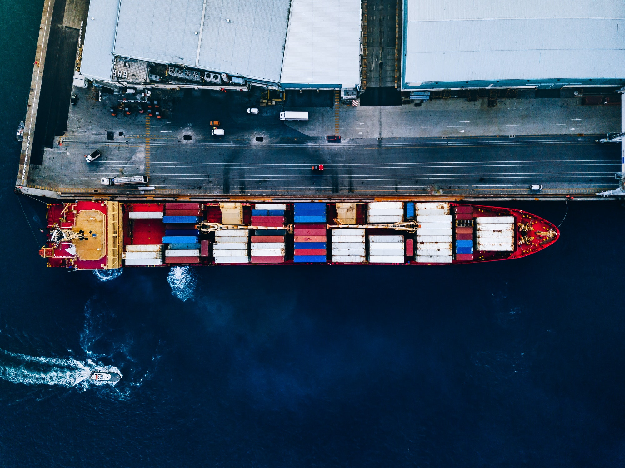 Aerial top view of industrial cargo container ship in terminal in Italy